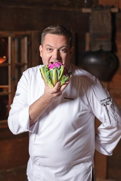 Der Küchenverantwortliche des Waldhotel Health & Medical Excellence beisst in ein Gemüsestrauss