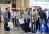 Eine Personenmenge steht an einer Ausstellung vor Ständen.
