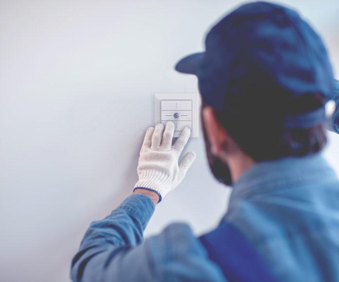 Ein Monteur installiert einen Taster an der Wand.